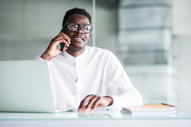 Casual hombre de negocios feliz hablando por teléfono fijo en la oficina, de pie apoyándose en el escritorio.