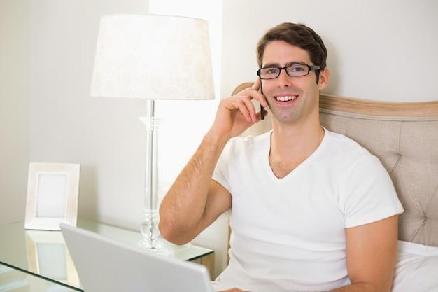 Casual hombre sonriente usando teléfono celular y computadora portátil en la cama