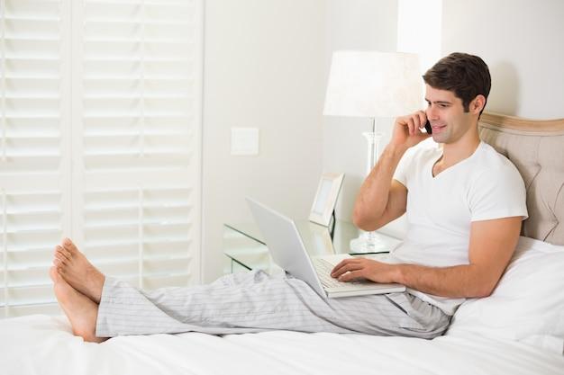 Casual hombre usando un teléfono celular y una computadora portátil en la cama