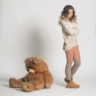 Casual joven sonriente en ropa de punto con gran oso de peluche suave