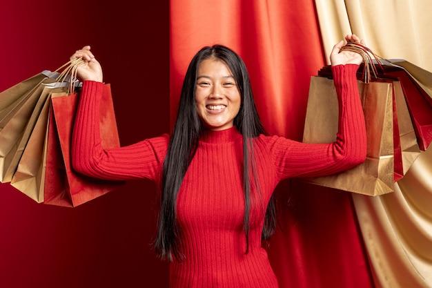 Casual mujer posando con bolsas de compras para el año nuevo chino