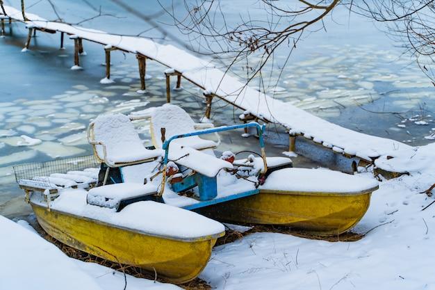 Catamarán azul y amarillo en un día de invierno, cubierto de nieve de pie cerca del río congelado y el puente de madera.