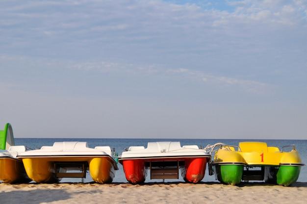 Catamaranes coloridos cerca de la orilla del mar en una playa desierta al amanecer