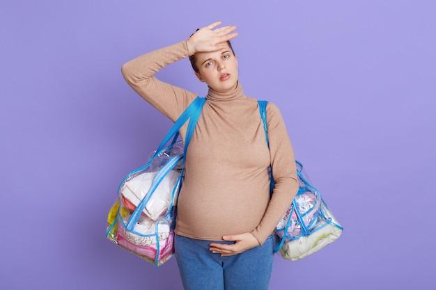 Caucásica joven hermosa embarazada, futura mamá cansada que siente fatiga y dolor de cabeza, se ve cansada y agotada, tocándose la frente, sosteniendo dos bolsas, yendo a la casa de maternidad.