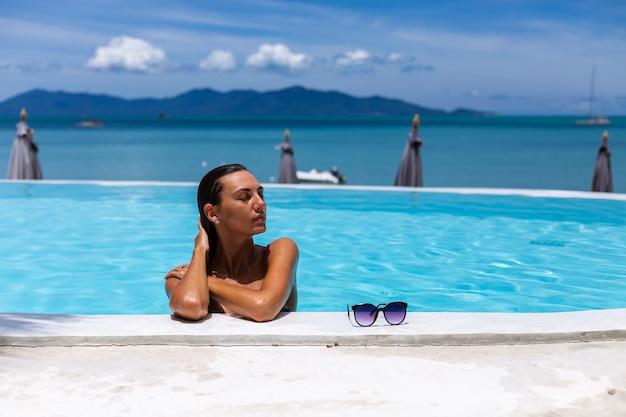 Caucásica mujer bronceada piel de bronce brillante junto a la piscina en bikini azul en un día soleado