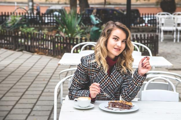 Caucásica niña feliz bebe café en una mesa de una cafetería de la calle.