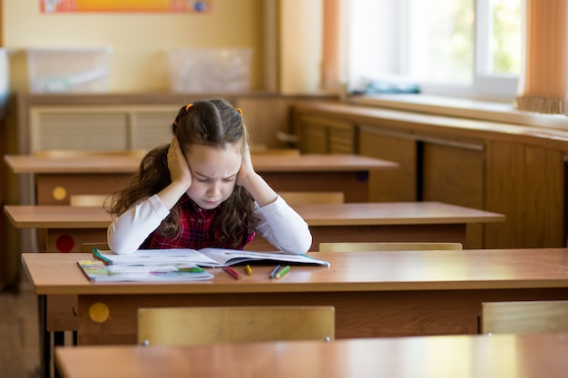 Caucásica niña sentada en el escritorio en la sala de clase y difíciles de aprender lecciones. preparación para exámenes, exámenes.