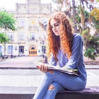 Caucásica pelirroja de pelo rizado sentada cerca de su universidad