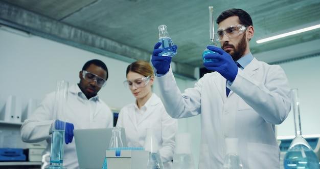 Caucásico apuesto trabajador de laboratorio médico haciendo análisis de un poco de líquido en los tubos de ensayo, mientras que sus compañeros de trabajo multiétnicos hablando en la escena.