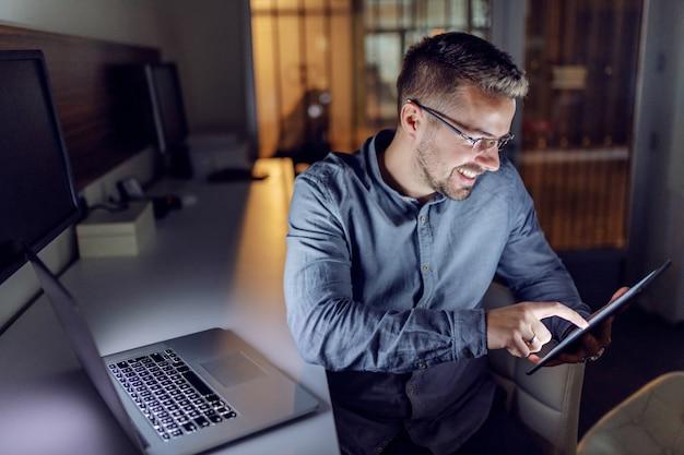 Caucásico barbudo sentado en la oficina a altas horas de la noche y con tableta.