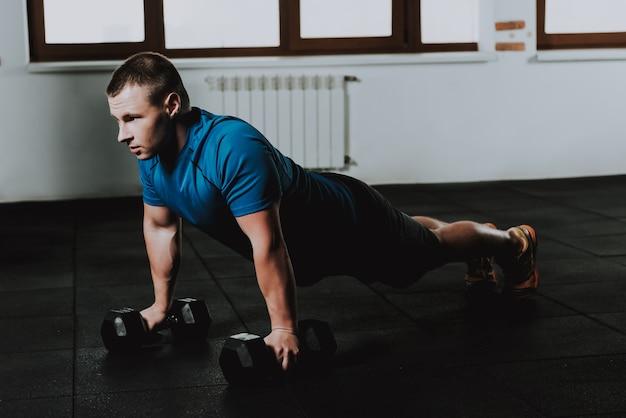 Caucásico deportista está haciendo ejercicio en gimnasio solo