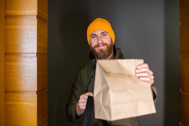 Caucásico entrega hombre manipulando la caja con comida adentro, dárselo al cliente en la puerta. servicio de entrega durante covid19.