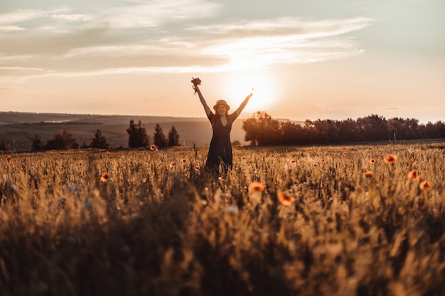 Caucásico feliz hermosa joven con un ramo de amapolas en sus manos en un campo de verano al atardecer. concepto de turismo, viajes y estilo de vida saludable.