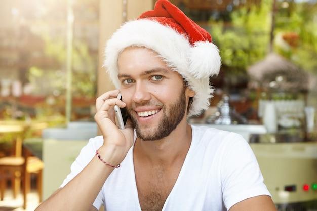 Caucásico joven alegre en sombrero de santa claus con conversación telefónica