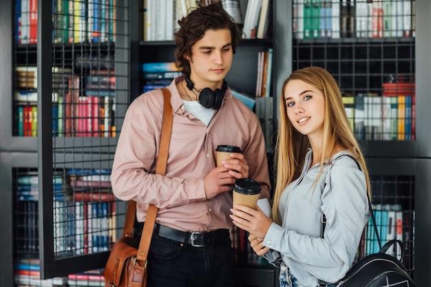 Caucásico, joven, hembra, y, hombre, estudiante, lee, libro, en, instituto, biblioteca, con, taza de café