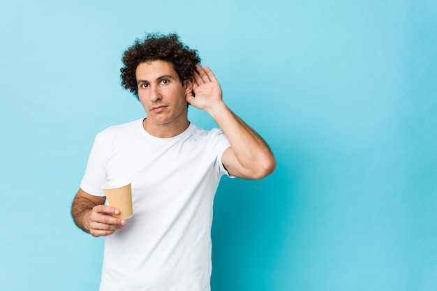 Caucásico joven rizado sosteniendo un café para llevar tratando de escuchar un chisme.