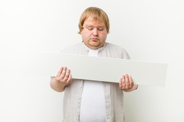 Caucásico loco gordo rubio con un cartel