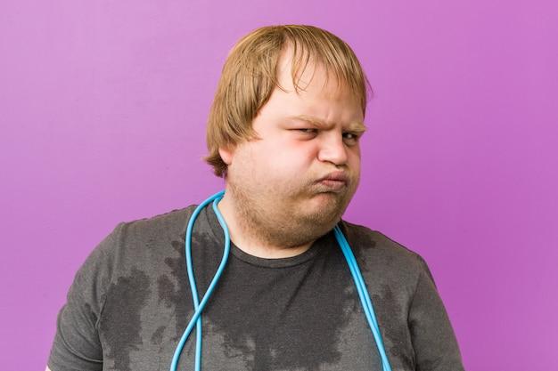 Caucásico loco gordo rubio sudando con una cuerda de saltar