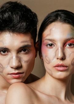 Cautivadora pareja posando con caras pintadas