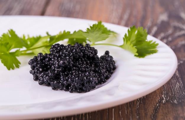 Caviar negro en un plato blanco con hierbas en mesa de madera
