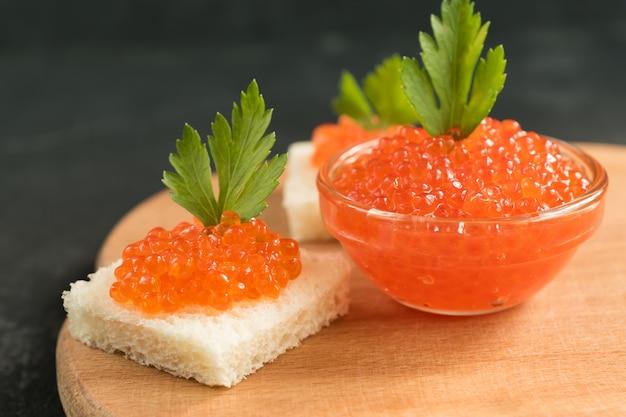 El caviar rojo delicioso en el pan de trigo sirvió con parseley en el escritorio de madera.