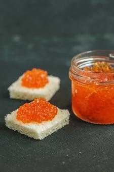 El caviar rojo sanwiched en el fondo gris, marisco. alimentación saludable y dieta. copiar espacio para texto