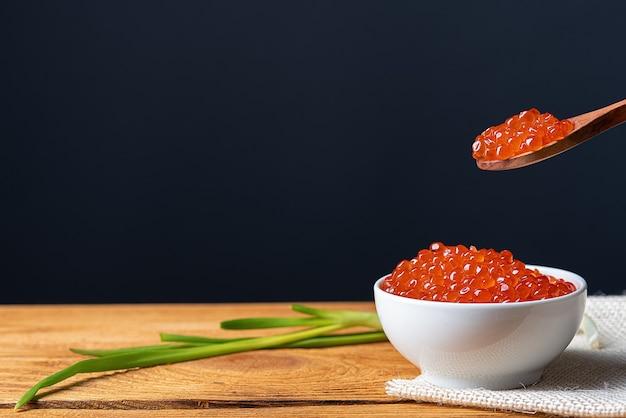 Caviar rojo en una taza de madera sobre un fondo de madera con una cuchara. lugar para publicidad, logotipo, etiqueta, maqueta, maqueta.