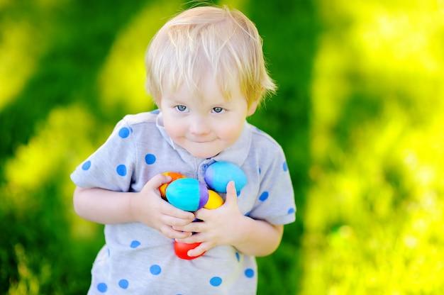 Caza del niño pequeño para el huevo de pascua en jardín de la primavera el día de pascua. pequeño niño lindo que celebra banquete