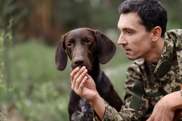 Cazador le da al perro para que huela en el bosque de verano