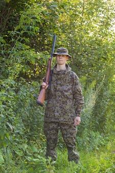 Cazador joven con una pistola en el bosque.