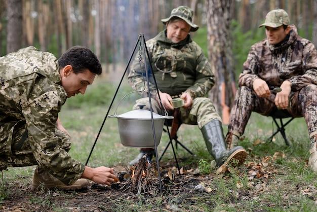 Cazador prende fuego en bosque cocinando comida de hoguera