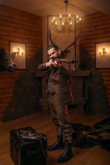 Cazador senior en ropa de caza tradicional retro apunta a la escopeta antigua contra el pecho viejo.