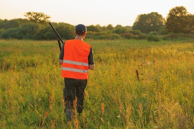 Cazador en la temporada de caza de otoño en puesta de sol.
