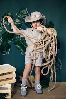 Cazador de vaquero chico serio en la selva con una cuerda se encuentra en el estudio sobre un fondo verde
