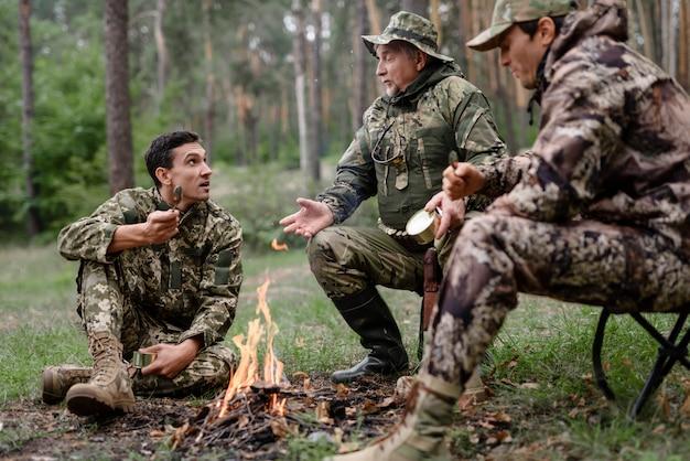 Los cazadores en el campamento de fuego, los hombres comen y hablan.