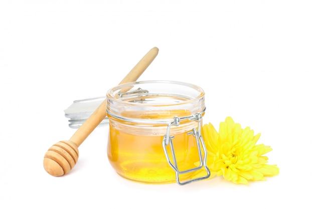 Cazo, crisantemo y tarro de cristal con miel aislado en blanco