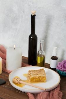 Cazo de madera y plato de cerámica blanco con botella de aceite esencial en mesa de madera