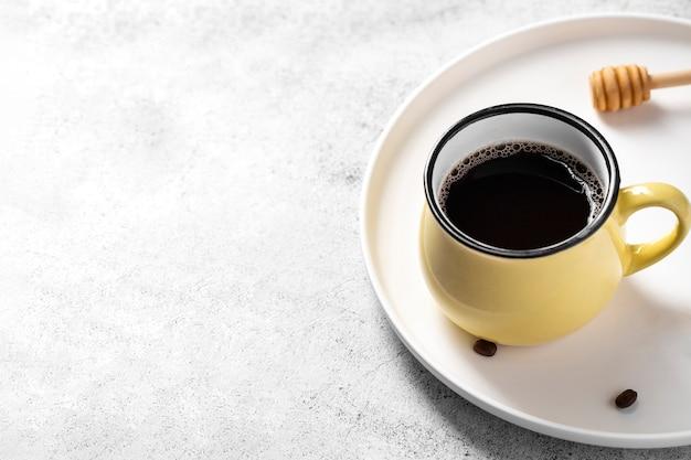 Cazo de miel de café de alto ángulo en bandeja con espacio de copia