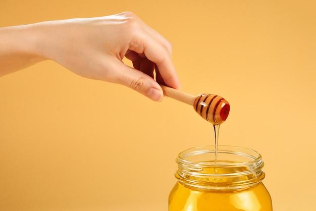 Cazo con miel en mano de mujer aislada