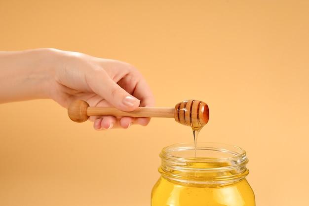 Cazo con miel en mano de mujer sobre fondo naranja. espacio para texto o diseño.