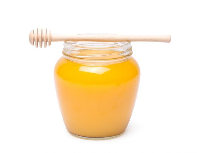 Cazo de miel y miel en frasco sobre fondo blanco.