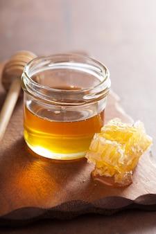 Cazo de nido de abeja y miel en tarro de mesa de madera
