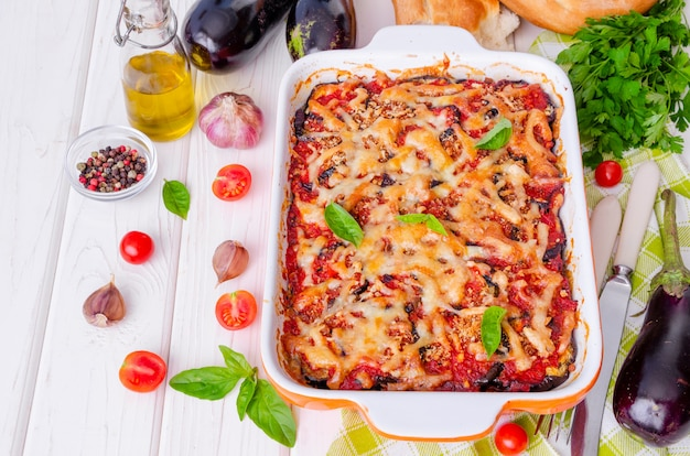 Cazuela de berenjenas con salsa de tomate, queso y albahaca fresca.
