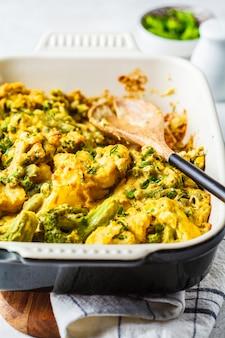 Cazuela de brócoli, guisantes y queso de coliflor en la fuente del horno.