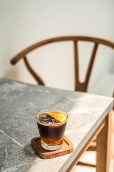 Ce café americano con naranja en la mesa