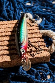 Cebo de pesca colorido en el panel de corcho sobre la red de pesca