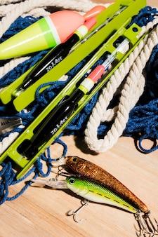 Cebo de pesca; línea de pesca y flotador de pesca en superficie de madera.