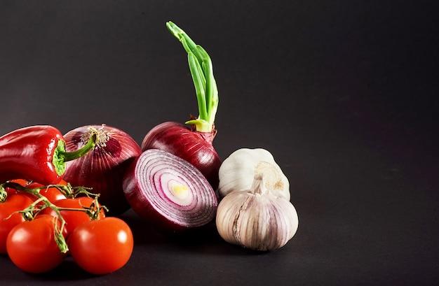 Cebolla y ajo y pimientos picantes y tomates aislados en un negro.