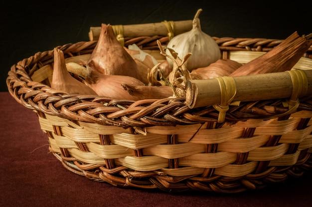 Cebolla cruda en cesta y sobre una mesa.