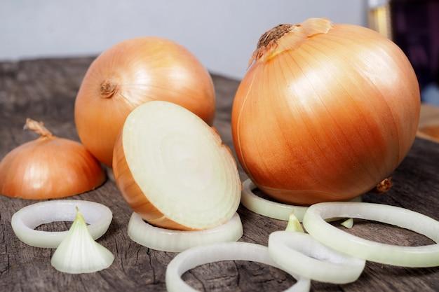 Cebolla fresca y rodajas de cebolla sobre fondo de mesa de madera vieja. comida natural